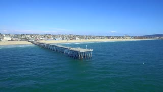 Drone view of beach town with dock from beach to ocean 3