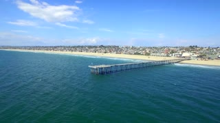 Drone view of beach town with dock from beach to ocean 4