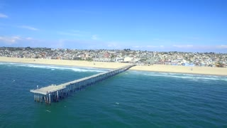Drone view of beach town with dock from beach to ocean
