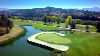 Drone view of beautiful golf course by pond and mountains 2