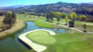 Drone view of beautiful golf course by pond and mountains