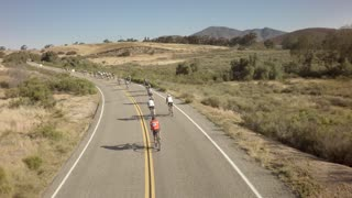 Drone view of bike race on open road with mountains in background 12