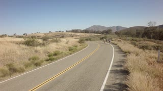 Drone view of bike race on open road with mountains in background 14