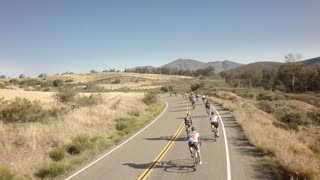 Drone view of bike race on open road with mountains in background 3