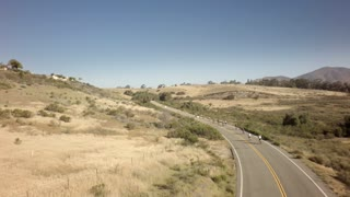 Drone view of bike race on open road with mountains in background 4
