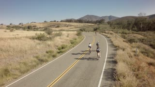 Drone view of bike race on open road with mountains in background 8