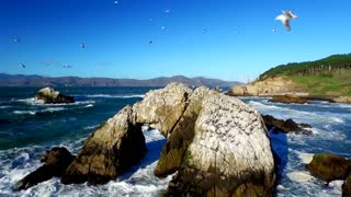 Drone view of choppy ocean and rocks by San Francisco beachside 2