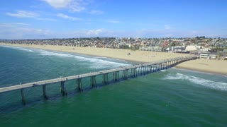 Drone view of dock over beach and town with blue sky