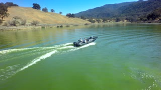 Drone view of motorboat traveling across a lake by mountains 2