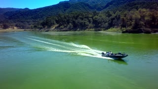 Drone view of motorboat traveling across a lake by mountains 4