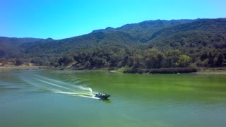 Drone view of motorboat traveling across a lake by mountains 5