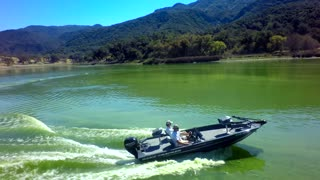 Drone view of motorboat traveling across a lake by mountains