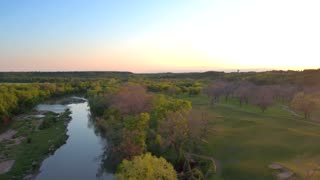 Drone view of reflective river next to trees and mountains 10