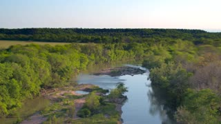 Drone view of reflective river next to trees and mountains 5