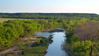 Drone view of reflective river next to trees and mountains 6