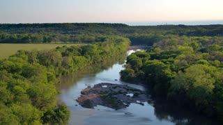 Drone view of reflective river next to trees and mountains 7