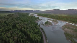 Drone view of river and forest by majestic mountains 2