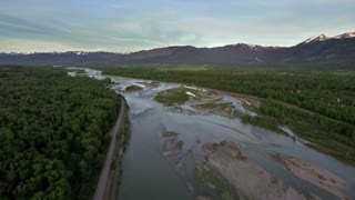 Drone view of river and forest by majestic mountains