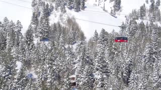 Drone view of ski lift traveling above snow covered trees