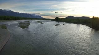 Drone view of sunset sky with snowcapped mountains and river 7