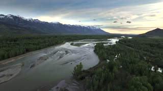Drone view of sunset sky with snowcapped mountains and river