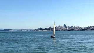 Drone view over water of sailboat cruising by San Francisco skyline