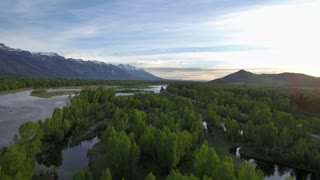 Evening drone view of snowcapped mountains by river 2