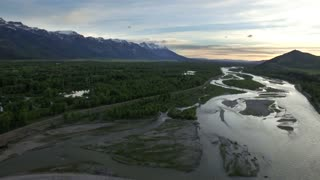 Evening drone view of snowcapped mountains by river