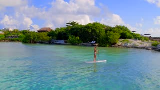 Girl Kayaks in Clear Blue Ocean