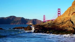 Golden Gate Bridge over waves crashing into beach mountainside 12
