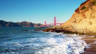 Golden Gate Bridge over waves crashing into beach mountainside 2