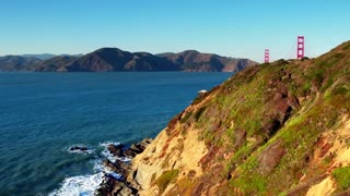 Golden Gate Bridge over waves crashing into beach mountainside 4