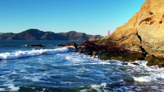 Golden Gate Bridge over waves crashing into beach mountainside 7