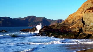 Golden Gate Bridge over waves crashing into beach mountainside 8