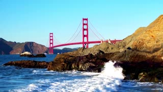 Golden Gate Bridge over waves crashing into beach mountainside 9