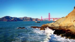 Golden Gate Bridge over waves crashing into beach mountainside