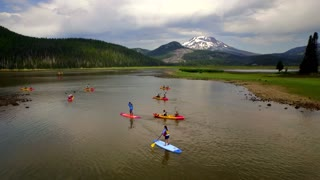 Group of people paddle board next to Oregon mountainside 2