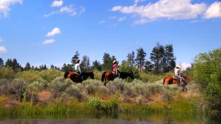Group of people ride horses along mountainside trail and water 2