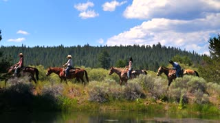 Group of people ride horses along mountainside trail and water 3