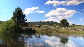 Group of people ride horses along mountainside trail and water