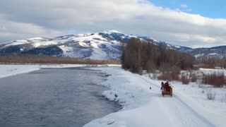 Horse and carriage follow dog alongside river and snow covered mountains 3