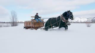 Horse and carriage travel alongside mountains in snow 2