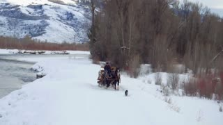 Horse and carriage travel alongside river and snow covered mountains