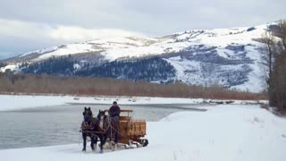 Horse pulls carriage through snow with mountains in the background