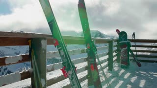 Isolated skis and snowboard by snow covered mountains