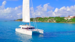 Luxury Catamaran Yacht Sailing off Tropical Coast From Aerial Drone 6