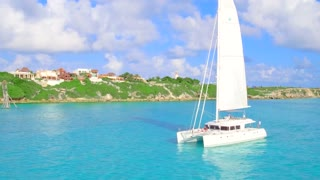 Luxury Catamaran Yacht Sailing off Tropical Coast From Aerial Drone