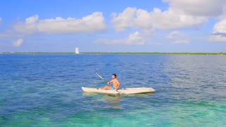 Man Kayaks in Clear Blue Ocean