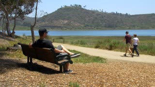 Man sits on park bench with view of water and mountainside palm trees 2