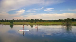 Paddle boarders ride on Oregon lake next to green forest and sunset sky 2